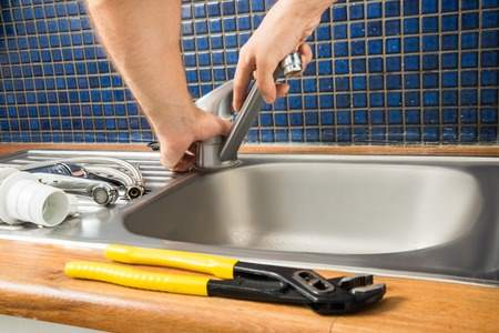 Image of a plumber working on plumbing of a kitchen sink and using a wrench on a tap..