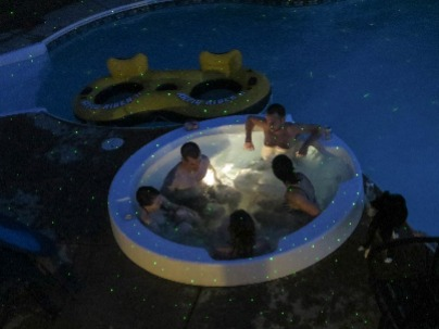 Image shows friends enjoying a hot tub together at night.