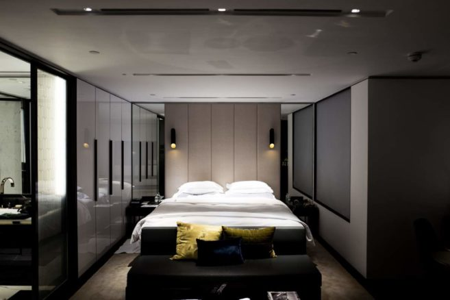Image shows a stylish grey walled bedroom with plenty of storage space in this modern bedroom design for small rooms.